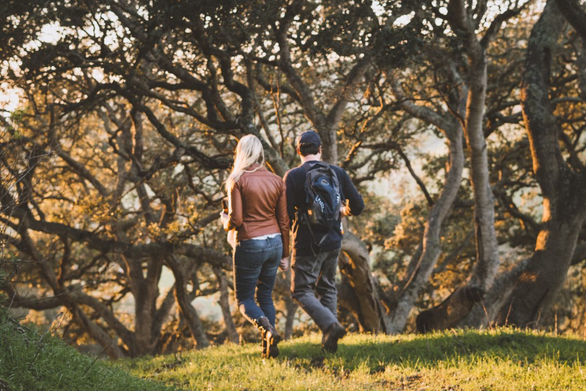 Candid photography of couple walking through the forest