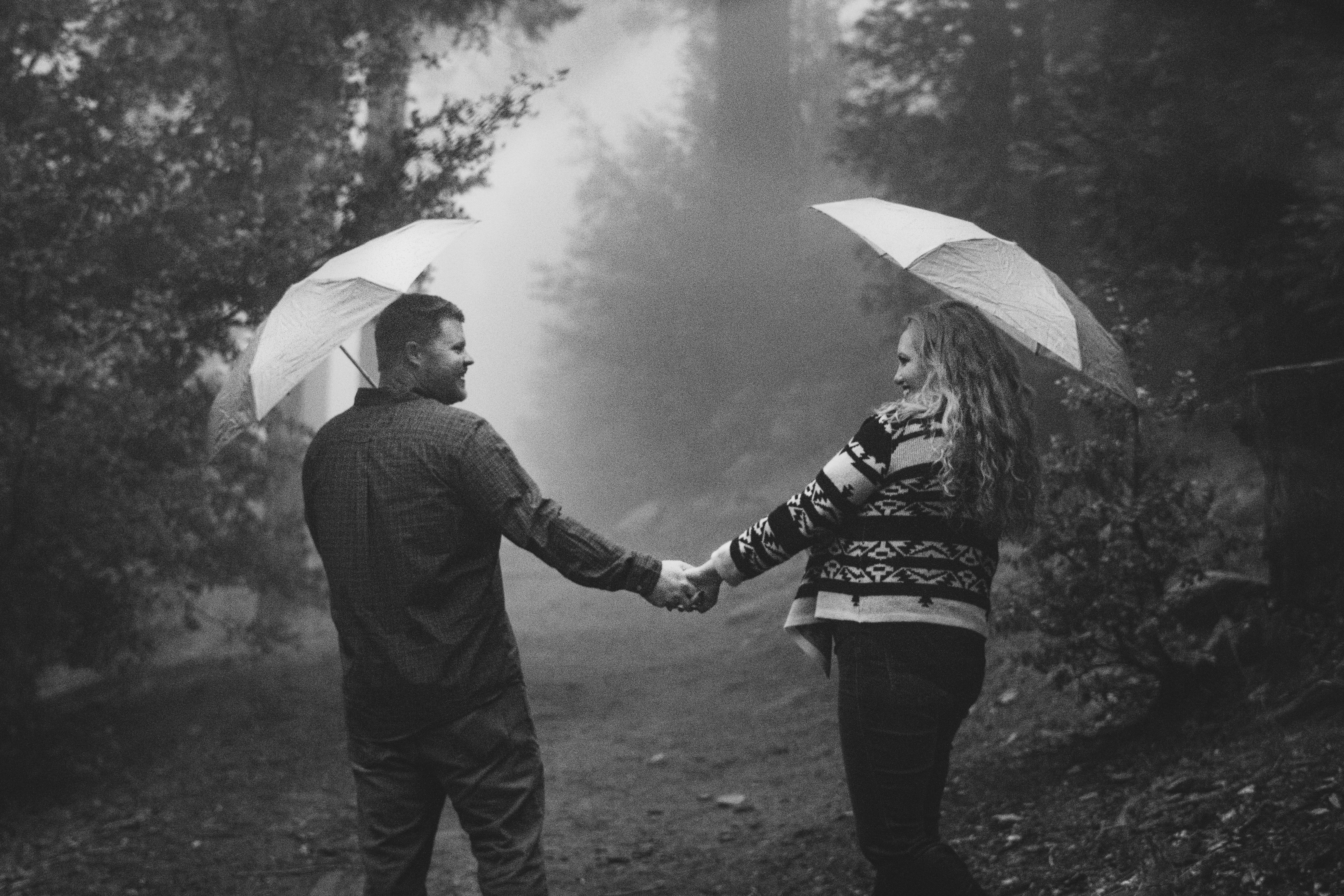 Couple Holding Hands in the Forest with Umbrellas