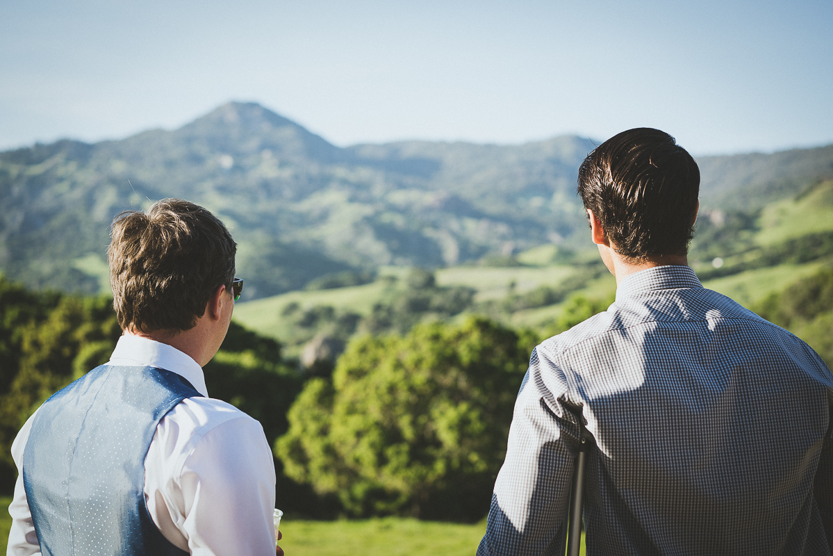 Groom and friends staring at the green mountains