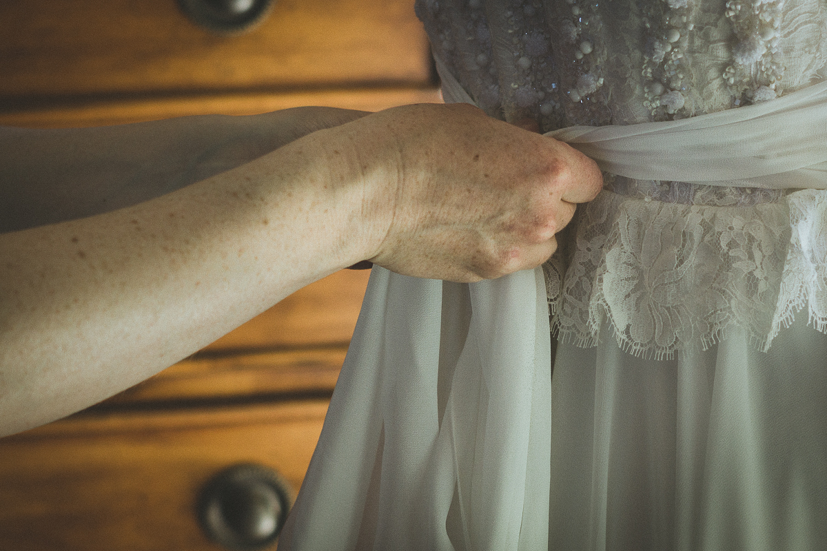 Bride's sister helping with the wedding dress