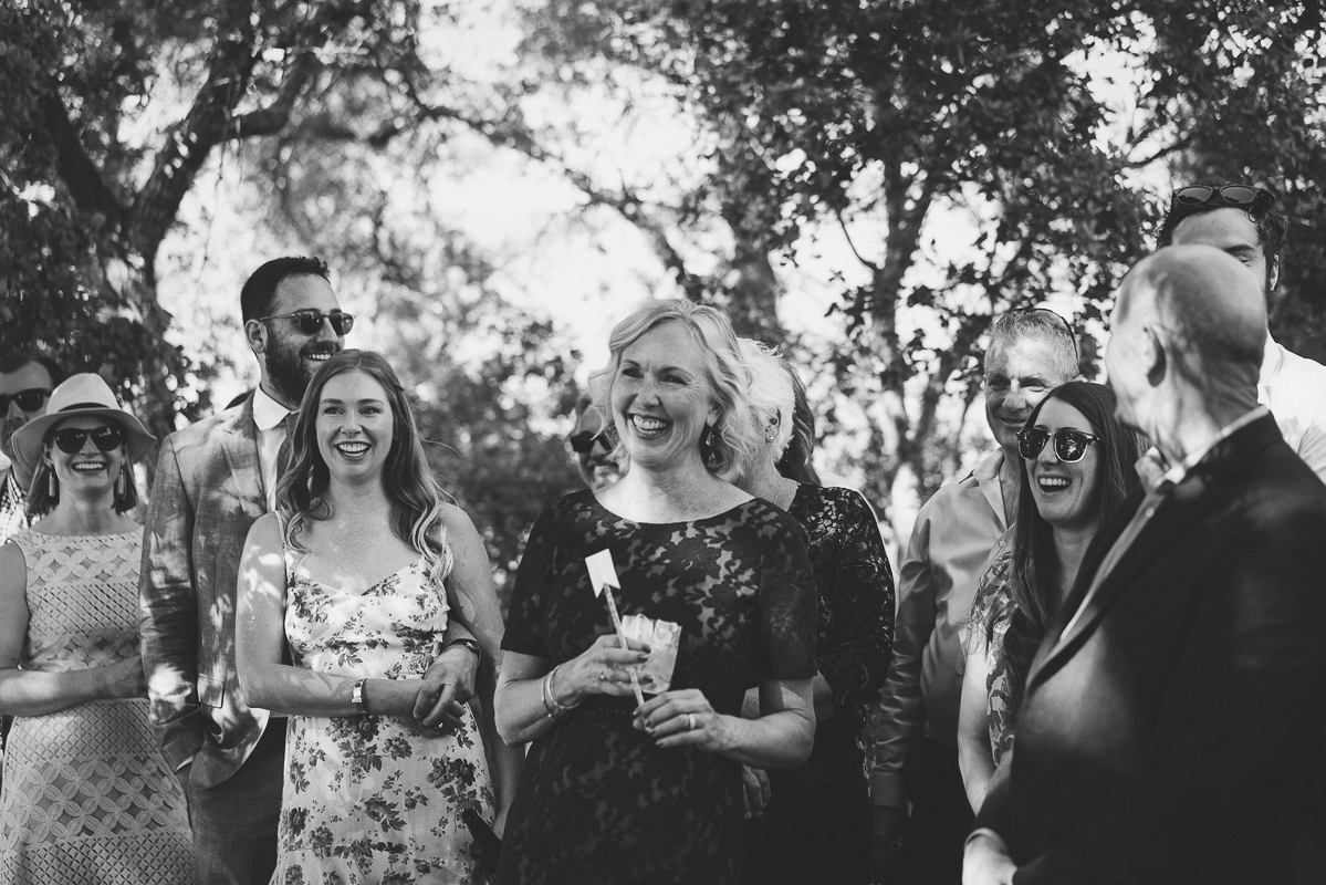 Black and white family and friends laughing at a wedding