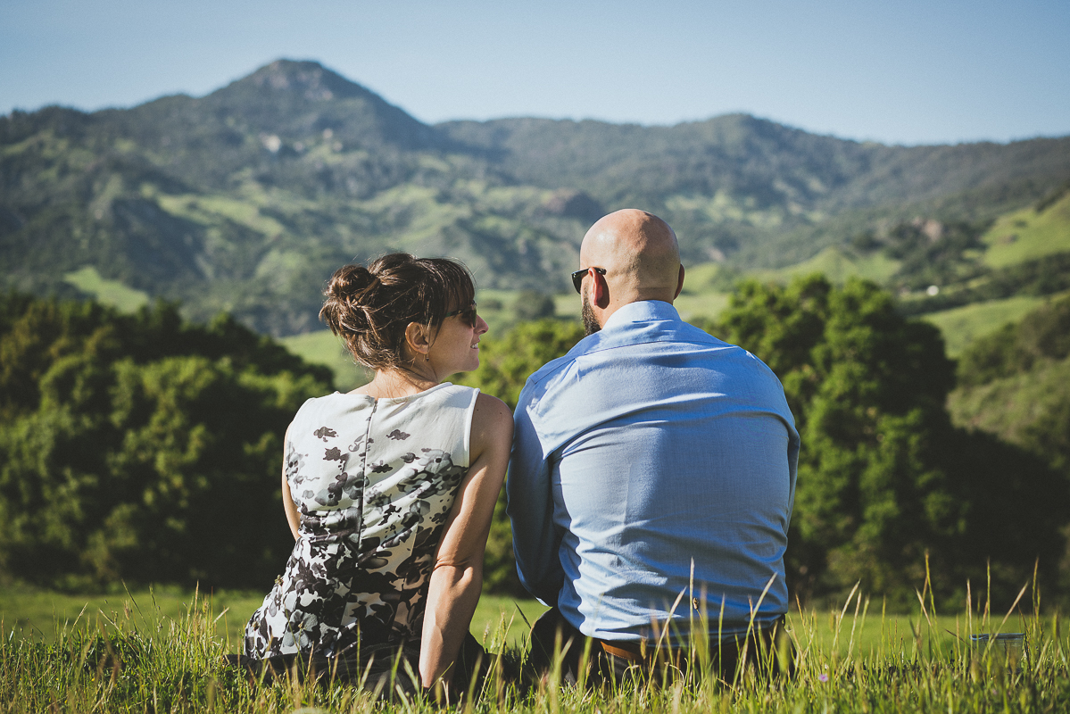 couple sitting in the grass by the mountain
