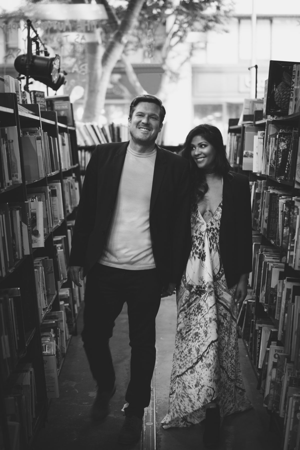 Lovers walking among books in Los Angeles California