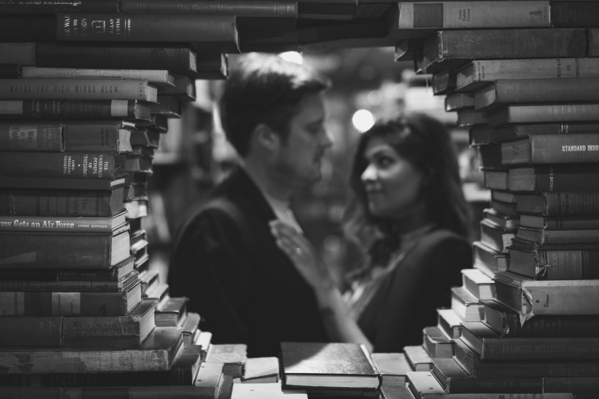 Black and white engagement pictures in circle of books The Last Bookstore