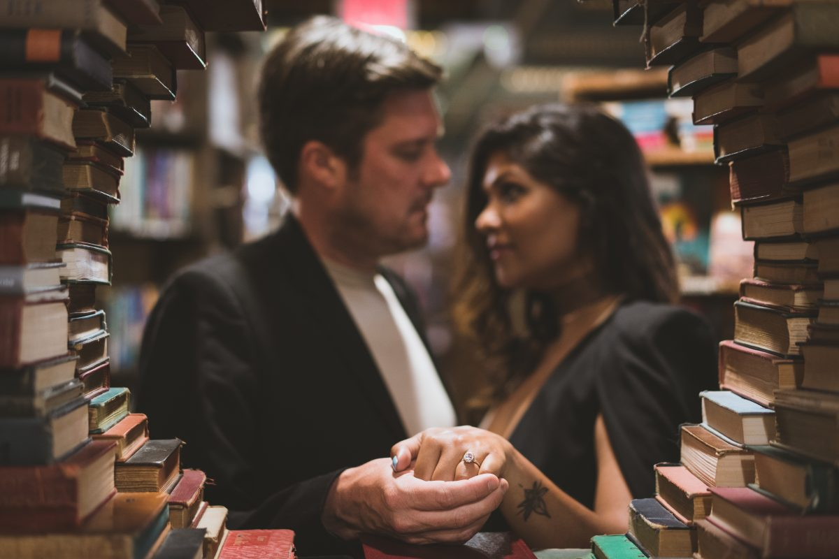 Engaged couple showing off ring by a circle of books