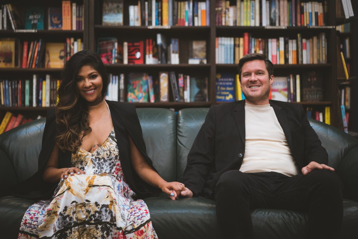Happy engaged couple surrounded by books