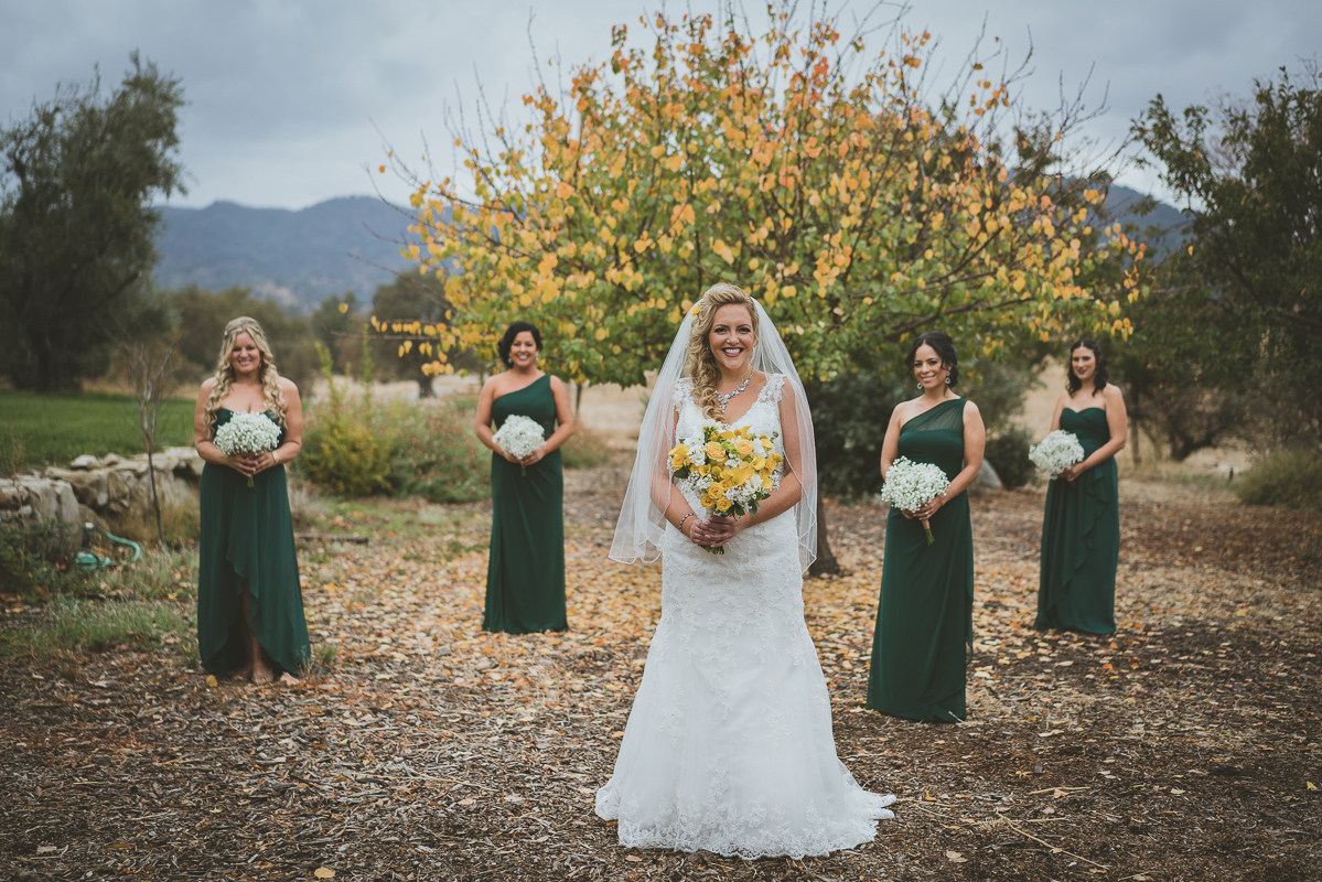 bride and her wedding party posing by fall tree
