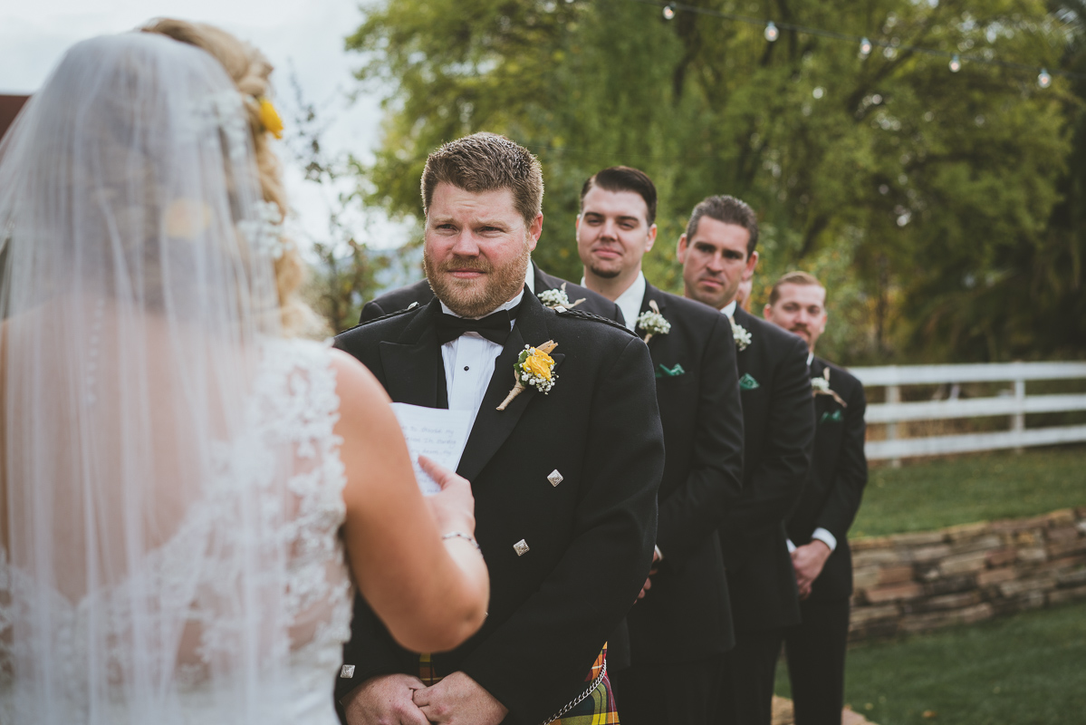 groom listening to bride read her vows