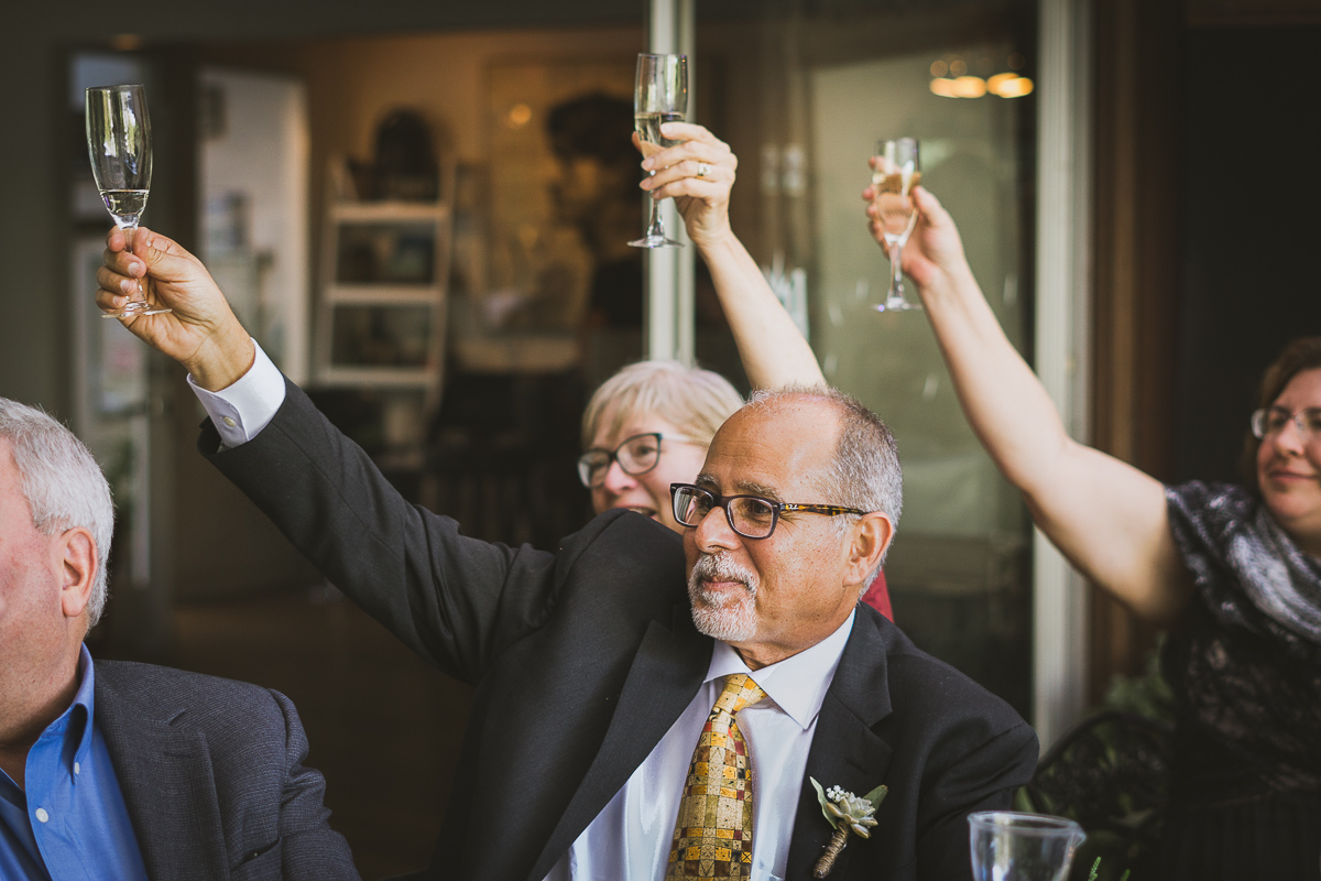 Father of the groom cheering after a toast