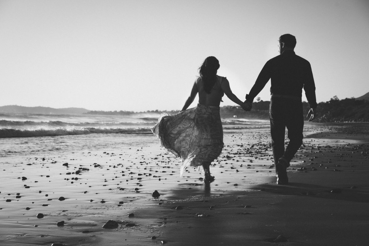 black and white walking on the beach, dress blowing in the wind