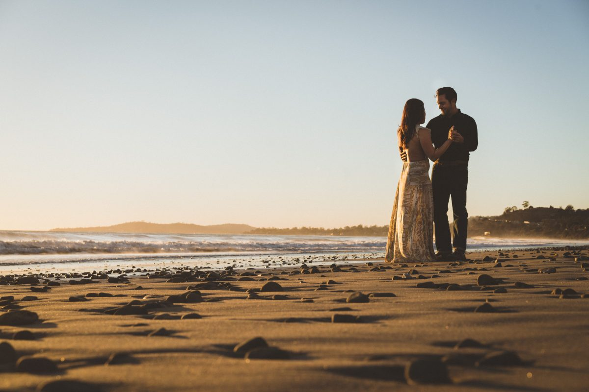 beautiful rocks on the beach, couple looking in each others' eyes during sunset