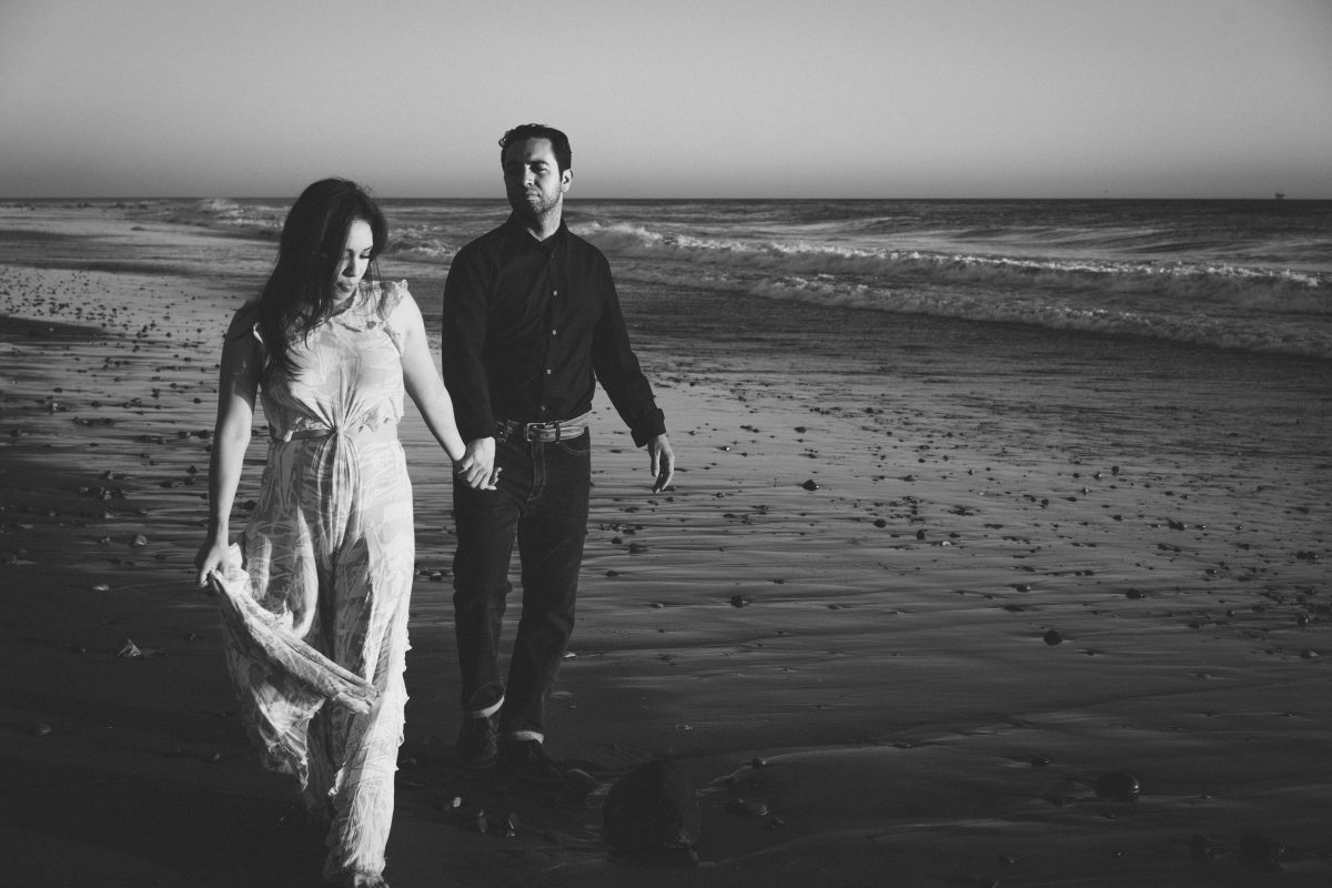 black and white couple with the ocean behind them