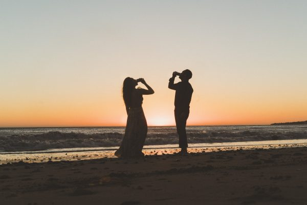 married couple drinking a local beer on the beach silhouette