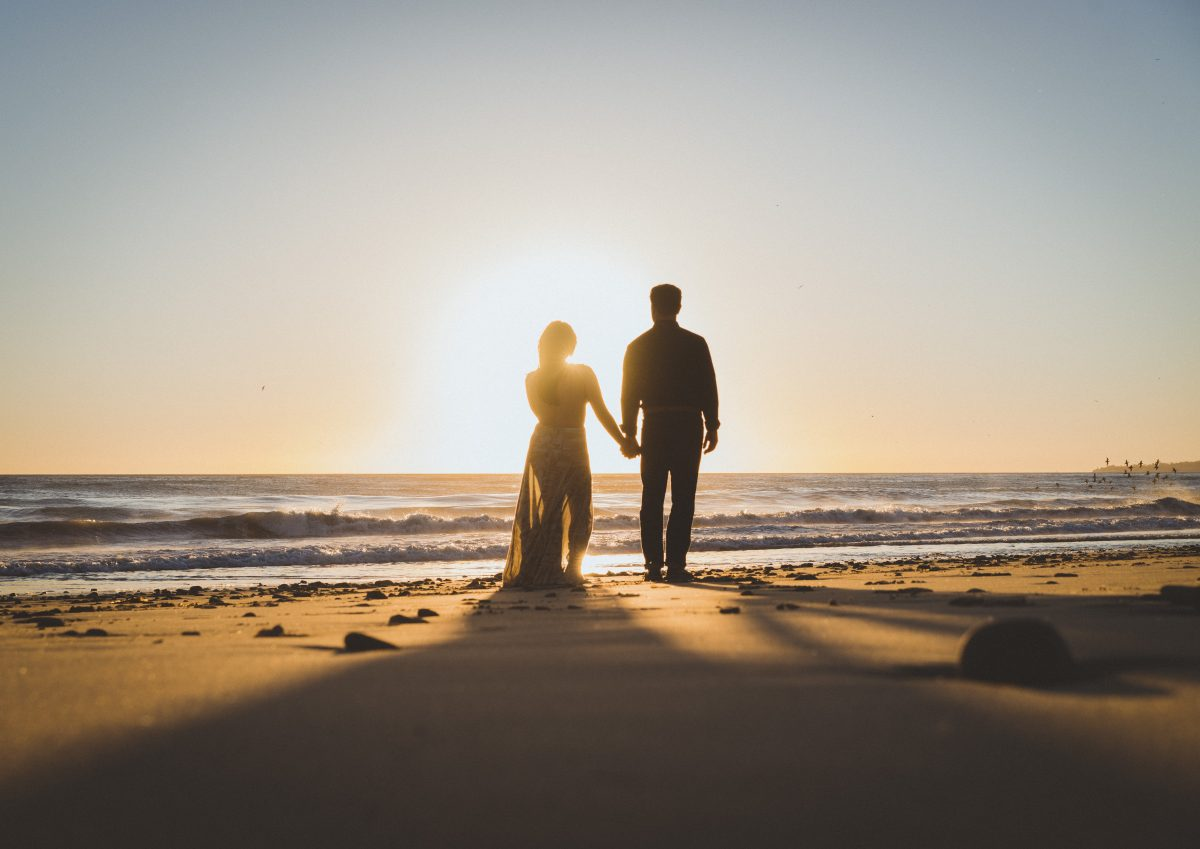 silhouette of couple holding hands and looking over the ocean as the sun sets