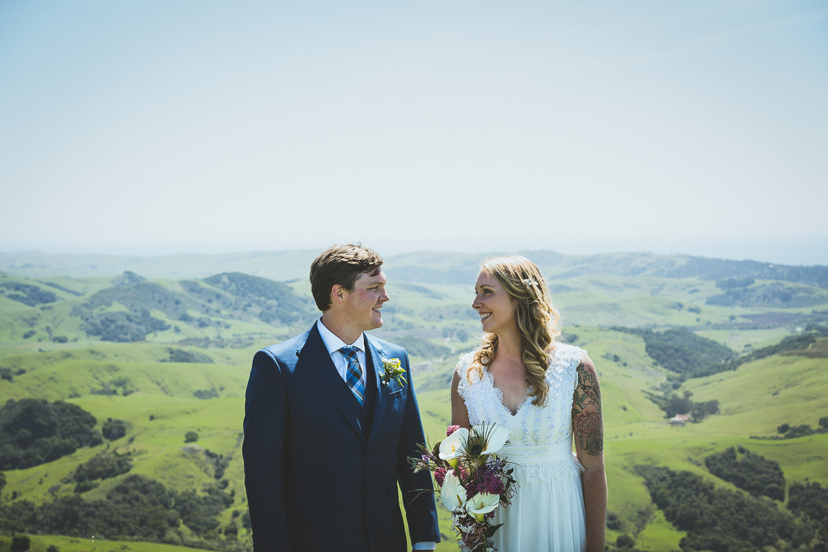 Bride and groom stare at each other in the mountains