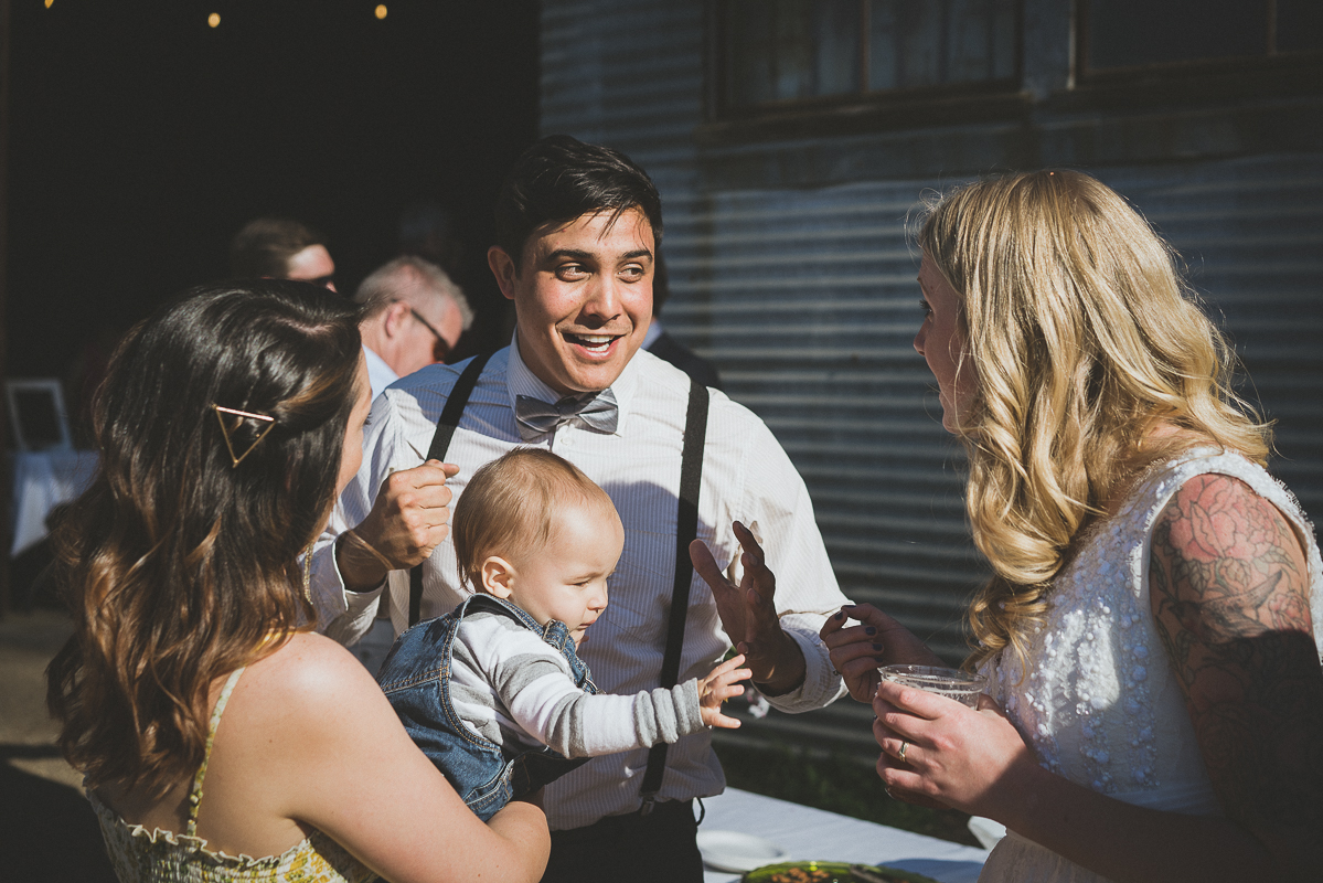 Baby reaching for bride's beer