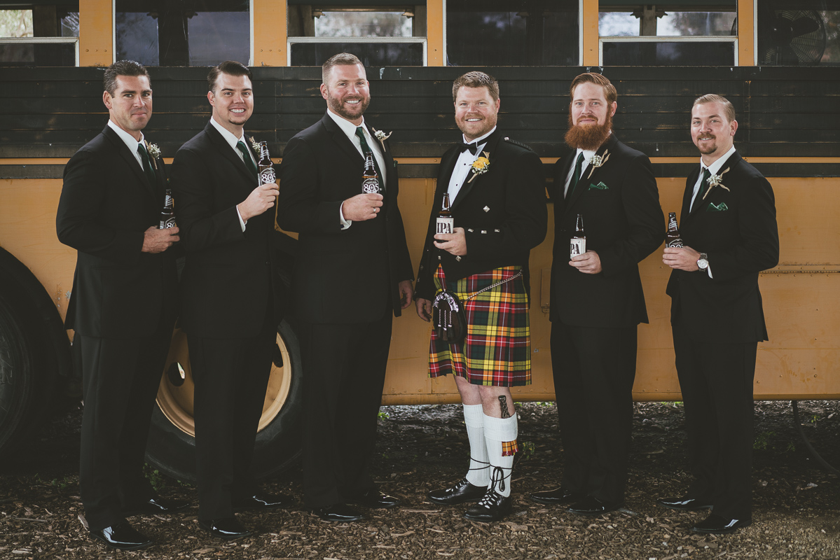 groom and groomsmen portrait by the bus