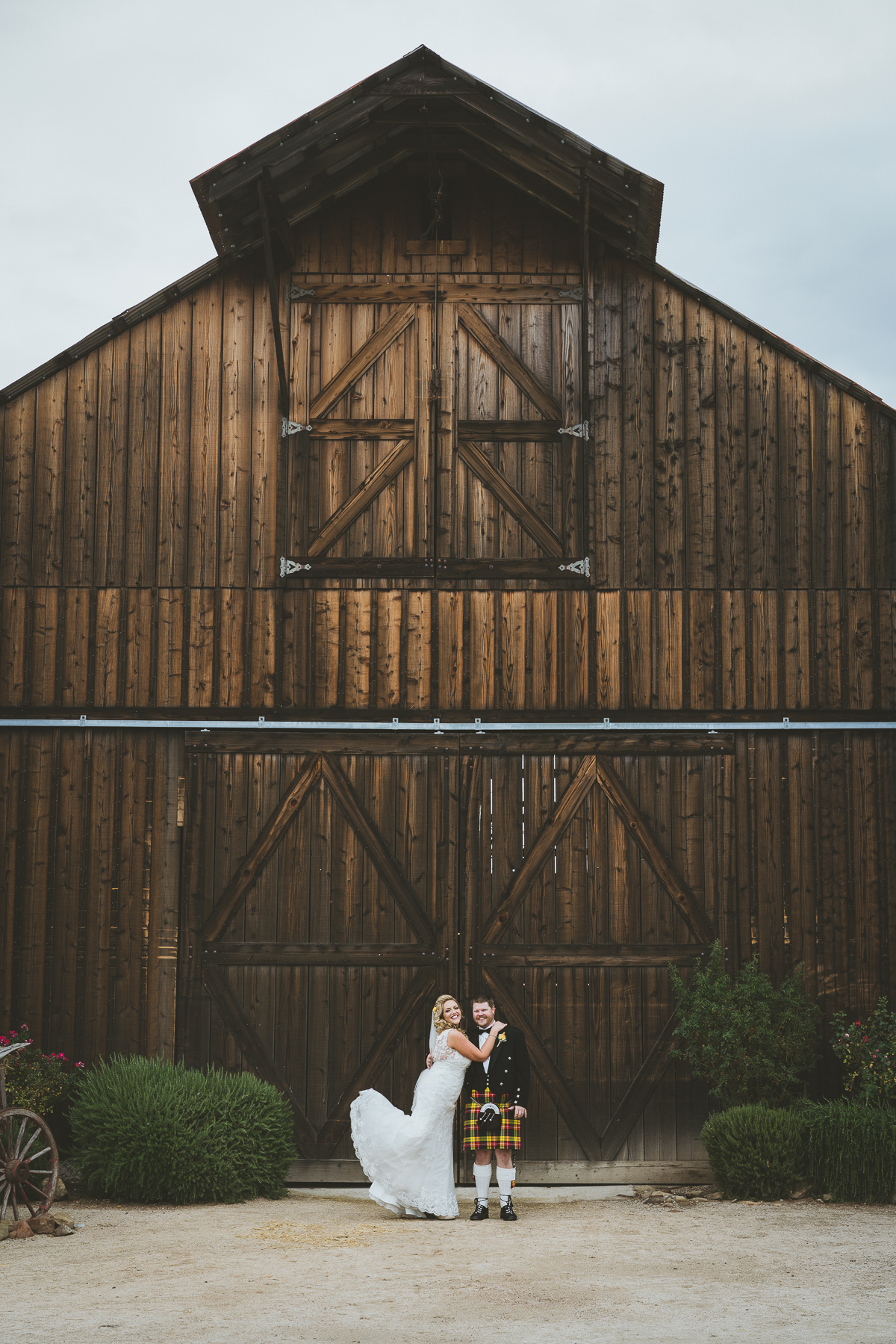 Happy couple posing in front of wedding barn