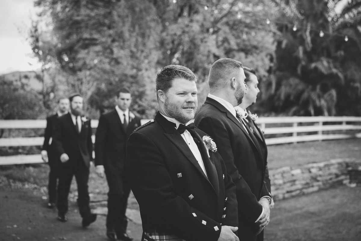 black and white candid of groom and his wedding party