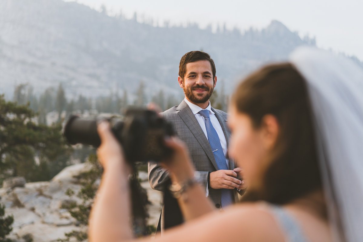 Groom watching his bride take a picture