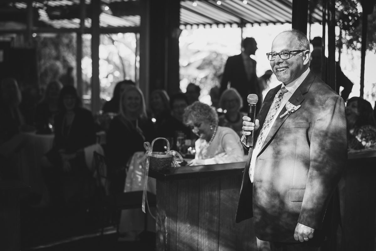Father of the groom giving a speech and smiling